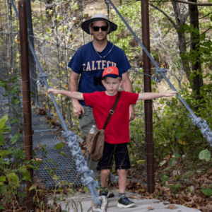 Parent with his cub scout leaving the bridge that spans the river at Camp McClintock