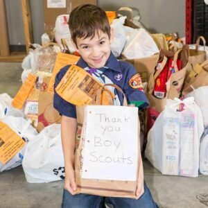 "A young boy kneeling in front of food donations holds a bag of food with a hand written ""thank you boy scouts!"" note"